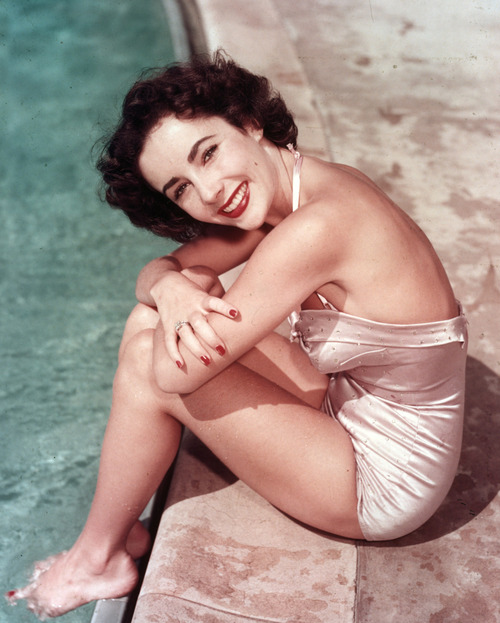 Elizabeth Taylor one peice swimsuit by the pool with red lips and nails